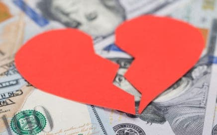 Broken paper heart over money