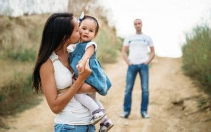 Young mother in white t-shirt and blue jeans with a small daughter in dress hugging and kissing with a father on the background